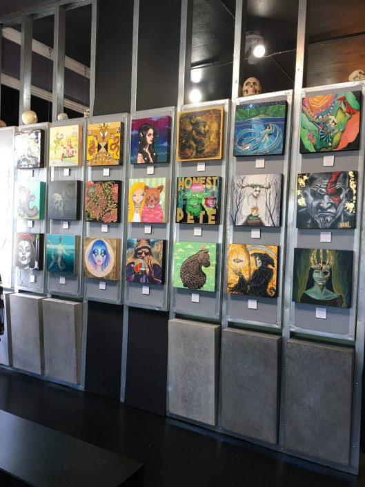 Right to Left View of Twenty One Paintings Hanging on Right Wall Inside of Black Amethsyt Tattoo Gallery
