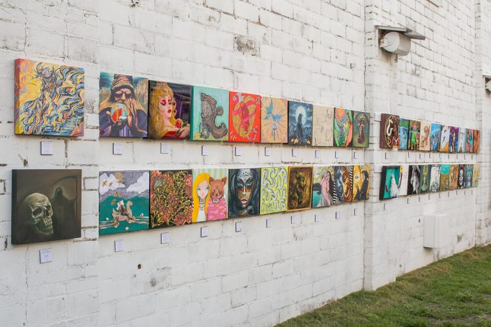 Paintings Lined Up Front to Back Along the Wall At Black Amethyst Tattoo Gallery Art Show