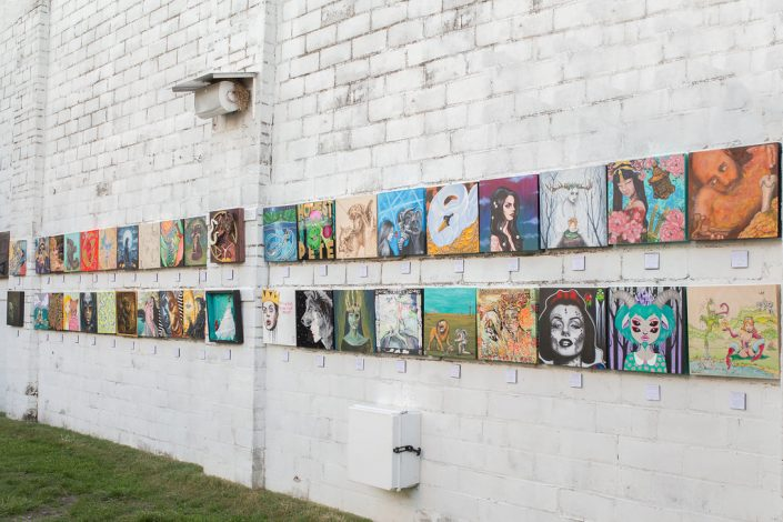 Paintings Lined Up Back to Front Along the Wall At Black Amethyst Tattoo Gallery Art Show