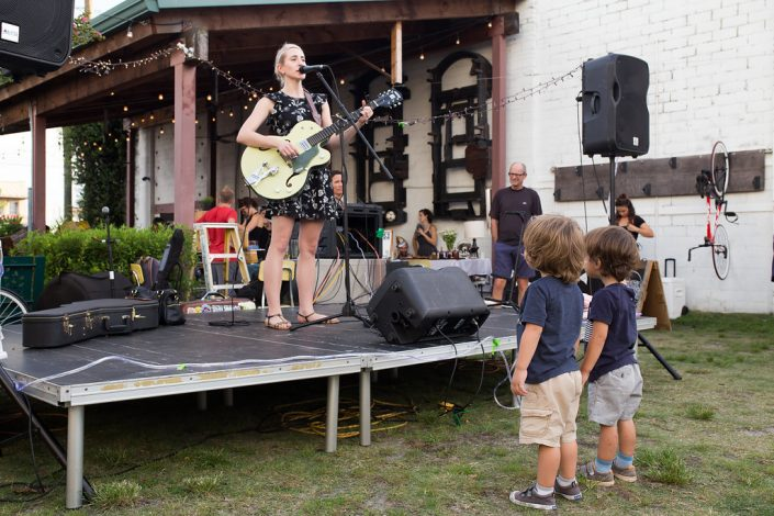Two Children Enjoying Woman Sing and Play Guitar at Black Amethyst Tattoo Gallery Art Show