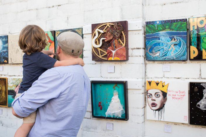 Man Carry Child While Enjoying Art at Black Amethyst Tattoo Gallery Art Show