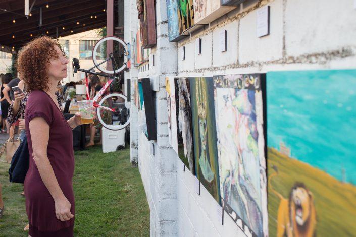 Woman in Burgundy Dress Enjoying Art With Beer at Black Amethyst Tattoo Gallery Art Show