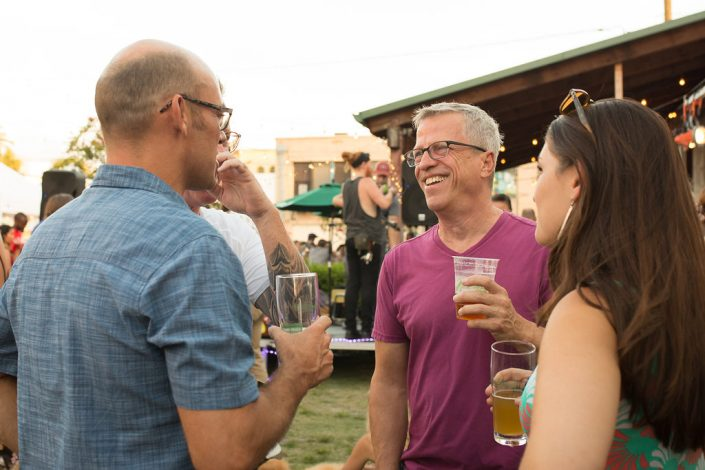 Candid Photo of Three Men and Woman Talking over beers and Black Amethyst Tattoo Gallery Art Show