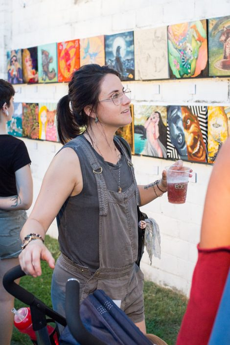 Woman Looking at Art with her Beer at Black Amethyst Tattoo Gallery Art Show