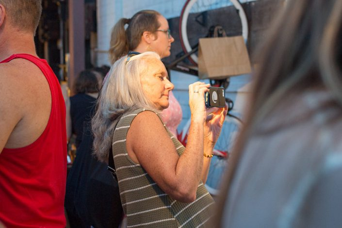 Older Woman Taking a Photo on Her Phone at Black Amethyst Tattoo Gallery Art Show